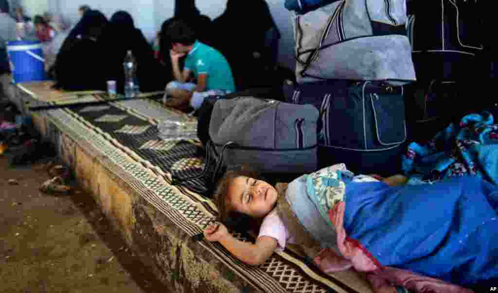 A Syrian girl who fled her home with her family due to fighting in Syria sleeps by her family's belongings at the Bab Al-Salameh border crossing in Azaz, in hopes of entering one of the refugee camps in Turkey, August 23, 2012.