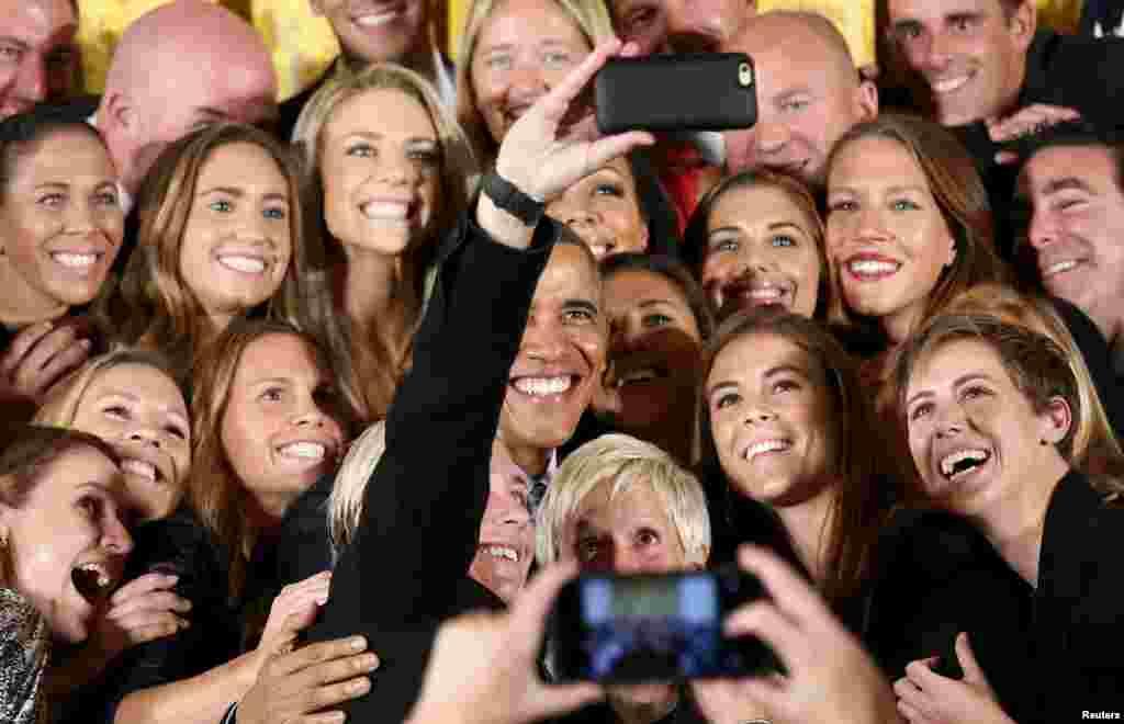 Tổng thống Mỹ Barack Obama chụp hình với cầu thủ kỳ cựu Abby Wambach khi ông chào đón đội tuyển bóng đá nữ quốc gia của Mỹ đến Tòa Bạch Ốc ở Washington để mừng chiến thắng của họ ở FIFA World Cup 2015 của nữ.