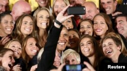 President Barack Obama poses for a selfie taken by veteran star player Abby Wambach as he welcomes the United States Women's National Soccer Team to the White House in Washington to honor their victory in the 2015 FIFA Women's World Cup, October 27, 2015.