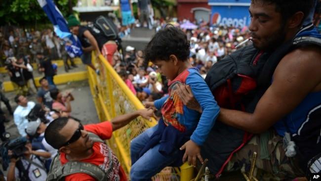 Un niño pasa la valla en la frontera mexicana mientras cientos de migrantes hondureños intenta cruzar la frontera hacia México, en Tecun Uman, Guatemala,
