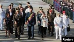En esta foto de archivo del 27 de noviembre, de 2017, se ve al presidente venezolano, Nicolás Maduro (centro) arribando a un desfile militar en Maracay, Venezuela.