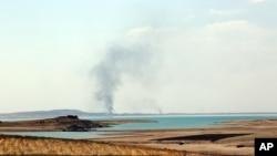 Khói bốc lên sau các cuộc không kích nhắm vào các chiến binh Nhà nước Hồi giáo tại đập Mosul, ngày 18/8/2014.