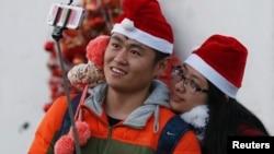 2014年12月24日,一对情侣带着圣诞帽在北京一所教堂里自拍。