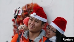 "FILE - A couple wearing Santa hats take a ""selfie"" at a Catholic church in Beijing, December 24, 2014."