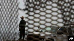 Un agente fronterizo es visto a través de la barda que separa México de Estados Unidos. El Senado rechazó aumentar el control en las fronteras como requisito para legalizar a millones de inmigrantes indocumentados.