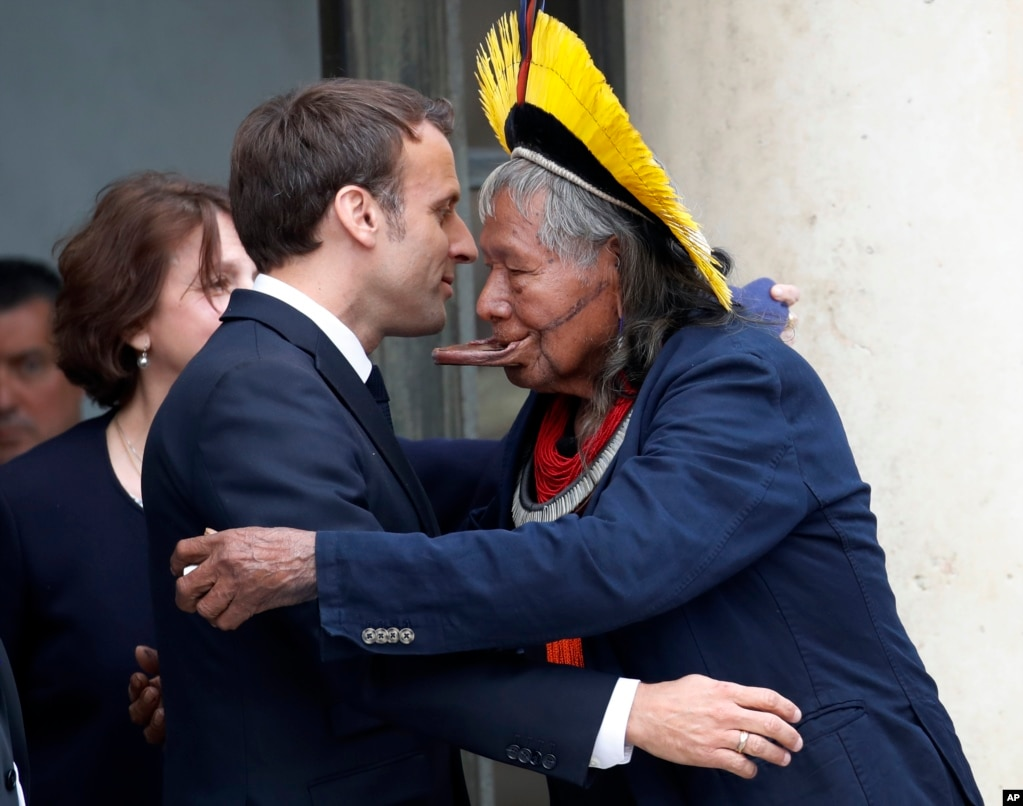 Kayapo tribal leader Raoni Metuktire, right, hugs French President Emmanuel Macron, after a meeting at the Elysee Palace, in Paris.