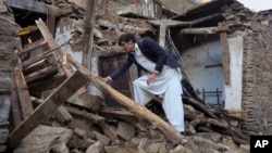A Pakistani youth examines an earthquake-damaged house in Mingora, the main town of Swat valley, Oct. 27, 2015.