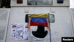 Un partidario del líder de oposición venezolano Juan Guaidó, a quien muchas naciones reconocen como el presidente interino del país, coloca una bandera nacional durante una manifestación contra el gobierno del presidente en disputa Nicolás Maduro. Julio 5, 2019.