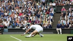 Serbia's Novak Djokovic slips on the grass during the men's singles second round match against South Africa's Kevin Anderson on day three of the Wimbledon Tennis Championships in London, Wednesday June 30, 2021. (AP Photo/Alastair Grant)