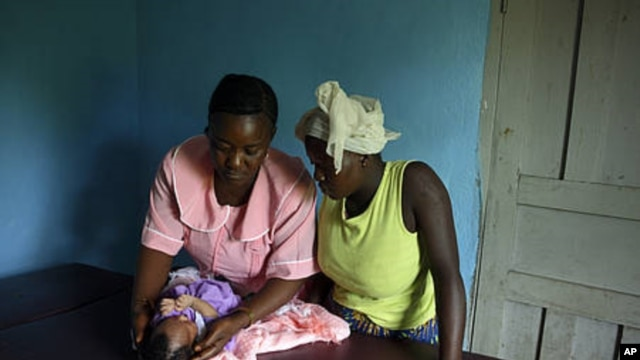 Margaret, MCHaid at Pendembu clinic examines a new born in Kallahun, Sierra Leone