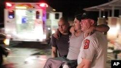 Para petugas tengah membawa korban badai, Miguel Morales, ke mobil ambulans di Granbury, Texas (15/5). Tornado telah melanda wilayah ini dan mengakibatkan puluhan rumah hancur.