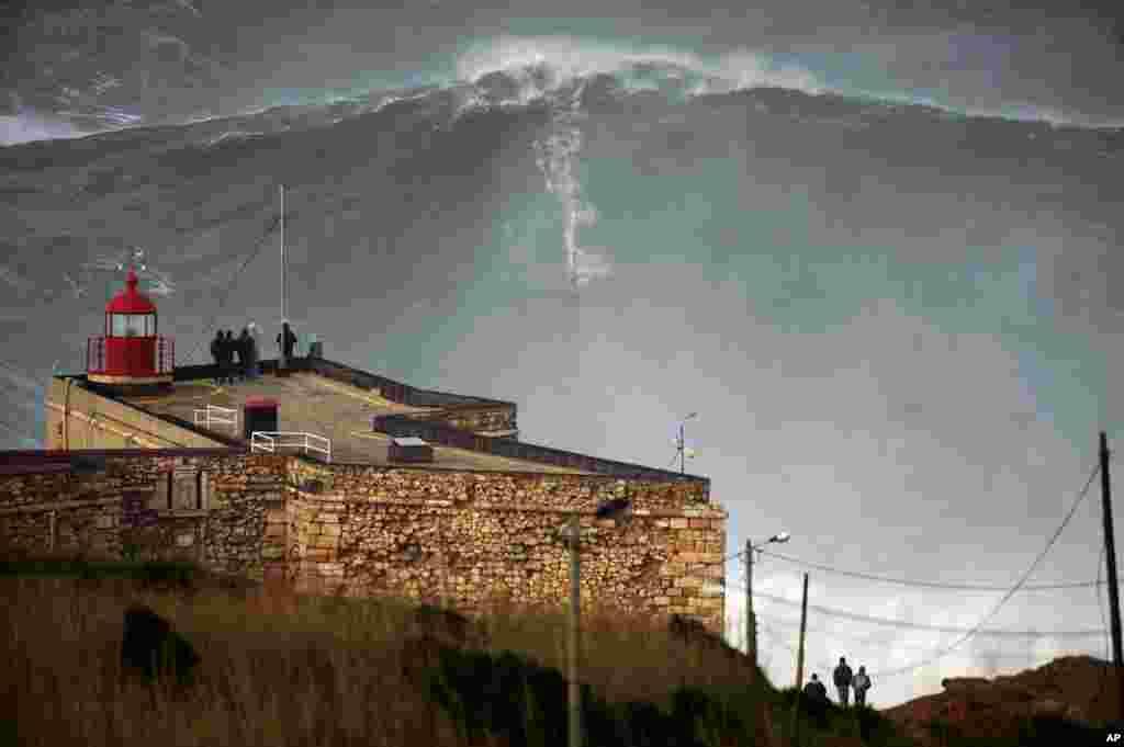 Ảnh chụp từ xa khi Garrett McNamara leo qua được ngọn sóng hơn 30 mét tại bờ biển Praia do Norte ở thành phố Nazare của Bồ Đào Nha.