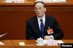 FILE - China's Politburo Standing Committee member Wang Qishan attends the opening of the annual full session of the National People's Congress (NPC), the country's parliament, at Great Hall of the People.