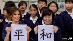 La primera dama de EE.UU. Melania Trump y Akie Abe, esposa del primer ministro japonés Shinzo Abe, muestran una imagen de caligrafía japonesa que hicieron durante una clase de niños de cuarto grado en la escuela primaria Kyobashi Tsukiji de Tokio, Japón. Nov.. 6 de 2017.