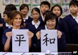 Las primeras damas de EE.UU. y Japón muestran su trabajo en caligrafía japonesa durante una visita a una escuela primaria de Tokio. Nov. 6 de 2017.