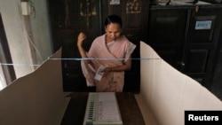 Seorang pemilih bersiap memberikan suaranya menggunakan mesin pemilih elektronik di sebuah TPS Dhekiajuli di distrik Sonitpur, negara bagian Assam, India timur laut.