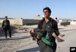 FILE - An Afghan man carries a wounded girl at the side of a suicide attack that killed civilians and a policeman in Lashkar Gah, the capital of Helmand province, south of Kabul, Afghanistan, March 16, 2015.