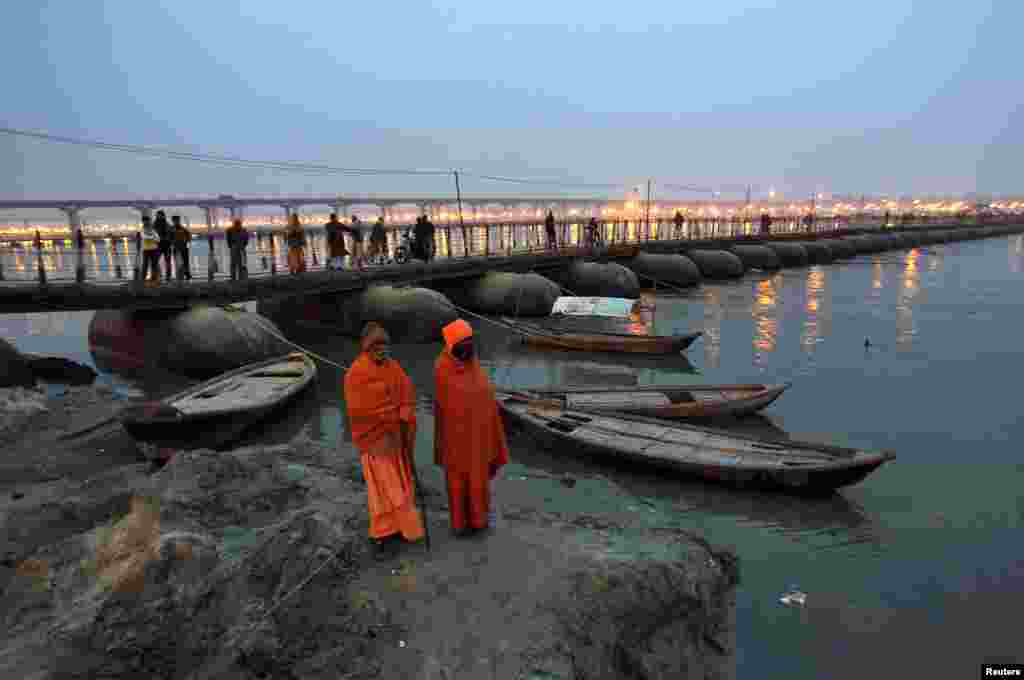 Sadhus - Hindu holy men - stand on the banks of river Ganges next to a pontoon bridge in the northern Indian city of Allahabad.