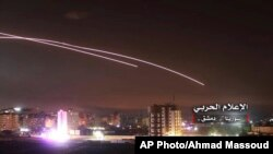 FILE - This photo provided by the government-controlled Syrian Central Military Media shows missiles rise into the sky as Israeli airstrikes hit air defense positions and other military bases, in Damascus, Syria, in May 2018.