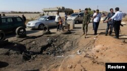 FILE- Army personnel look at the site of an explosion at an army checkpoint in Barsis, east of Benghazi, Libya, June 12, 2014.