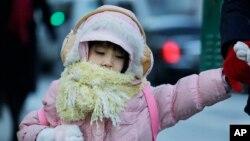 Una niña desafía el intenso frío en camino a la escuela en la ciudad de Nueva York, este jueves.