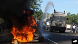 A police truck extinguishes a burning highway maintenance vehicle, after police dispersed protesters blocking a toll road and encouraging drivers not to pay, in Zambrano, north of Tegucigalpa, Honduras, Oct. 3, 2016. Groups organized by opposition political party LIBRE blocked major highways in multiple locations to protest against highway tolls.