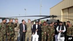 ប្រធានាធិបតីអាហ្វហ្គានីស្ថាន Ashraf Ghaniឈរថតរូតជាមួយនឹងប្រធានាធិបតីអាមេរិកនិងមន្រ្តីយោធាក្នុងស្រុកបន្ទាប់ពីទទួលបានឧទ្ធម្ភាគចក្រ Black Hawk ២ ពីរដ្ឋាភិបាលអាមេរិកនៅបន្ទាយអាកាស Kandahar Air Field ប្រទេសអាហ្វហ្គានីស្ថានកាលពីថ្ងៃទី០៧ តុលា ២០១៧។