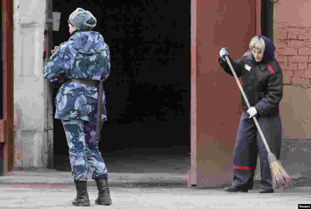 A prison officer stands guard as an inmate sweeps the floor inside female prison camp Number 22 in Russia's Siberian city of Krasnoyarsk.