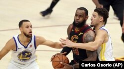 LeBron James aux prises avec Klay Thompson et Stephen Curry (30 ans) des Golden State Warriors (Photo AP / Carlos Osorio- Archives)