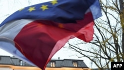 An unseen protester waves the flags of Poland and the European Union in front of the Polish Constitutional Court after a sentence regarding the appointment of judges, Warsaw, Dec. 3, 2015.