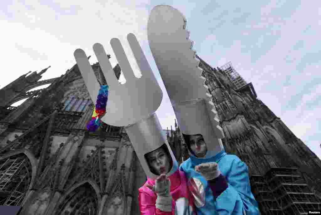 """Women dressed in costumes for """"Weiberfastnacht"""" (Women's Carnival) celebrate in front of Cologne's Cathedral, Germany."""