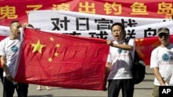 "Chinese protesters hold banners reading ""Declare war against Japan"" and ""Japan get out of Diaoyu islands"" during a protest outside the Japanese Embassy in Beijing Aug. 15, 2012."