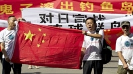 Chinese protesters hold banners reading