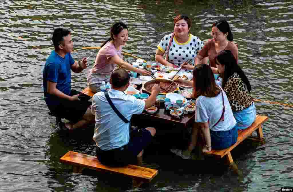 무더위가 찾아온 중국 쓰촨성 충칭의 관광명소에서 주민들이 계곡에 발을 담근 채 훠궈(중국식 샤부샤부)를 먹고 있다.