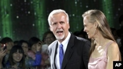 Film director James Cameron walks with his wife Suzy Amis on the red carpet during the opening ceremony of the second Beijing International Film Festival at the National Convention Center in Beijing, April 23, 2012.
