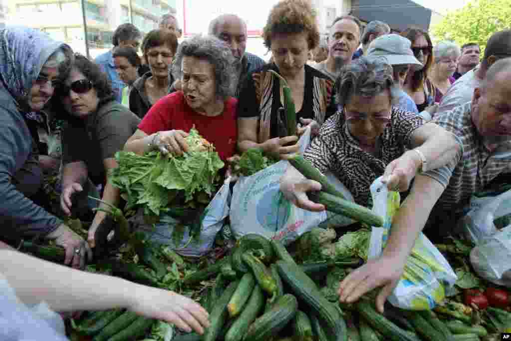 Người dân Hy Lạp trên đường phố Athens tranh nhau nhận rau cải tươi của Hiệp hội Nông dân. Hiệp hội đang biểu tình bằng cách lập ra những xe phân phát rau cải miễn phí cho đám đông.
