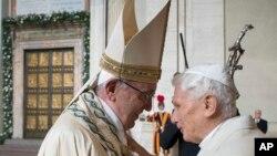 Le pape François, à gauche, donne une accolade au pape émérite Benoît XVI, à droite, avant d'ouvrir la Porte Sainte, vu dans l'arrière-fond, au cours d'une cérémonie marque le début de l'Année sainte, au Vatican, 8 décembre 2015.