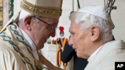 FILE - Pope Francis, left, and Pope Emeritus Benedict XVI hug at a Vatican ceremony, Dec. 8, 2015. Benedict shares his thoughts on the papacy in a new book, 'The Last Conversations.'