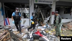 Security personnel inspect the Kok Po district office after being attacked by a group of gunmen in Pattani province, south of Bangkok, Sept. 11, 2014.