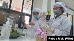 Mahasiswa Fakultas Farmasi Ubaya sedang memasukkan hand sanitizer bentuk gel ke dalam botol kemasan. (Foto: VOA/ Petrus Riski)