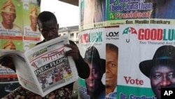 Nigerian man read a local newspapers with headlines, Independent National Electoral Commission flops, over a Portrait of Nigeria President Goodluck Jonathan in Lagos, April 3, 2011