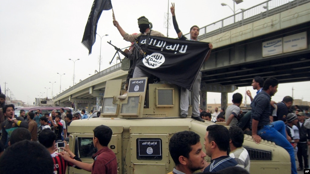 FILE - Islamic State group militants hold up their flag as they patrol in a commandeered Iraqi military vehicle in Fallujah, Iraq, March 30, 2014. The United States Friday sanctioned three members of the Islamic State who were featured in a beheading video distributed by the group and accused of luring recruits in Southeast Asia.