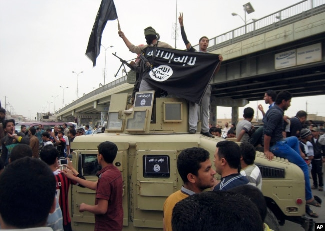 FILE - Islamic State militants hold up their flag as they patrol in a commandeered Iraqi military vehicle in Fallujah, Iraq, March 30, 2014. The terror group found a foothold in Somalia in October 2015, and is working to build up its presence there.