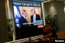 FILE - A woman reads a newspaper as monitors showing the meeting between U.S. President Donald Trump and Israeli Prime Minister Benjamin Netanyahu in Washington are seen next to a coffee shop in Tel Aviv, Israel, Feb. 15, 2017.