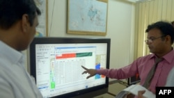 FILE - A Pakistani team member of Met Office's Tsunami Early Warning Center collects real time data on a computer from Indonesian, Australian and Indian centers in Karachi, Sept. 10, 2014.