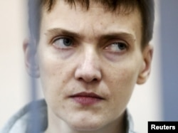 FILE - Ukrainian military pilot Nadiya Savchenko looks out from a defendants' cage during a court hearing in Moscow, Russia, May 6, 2015.