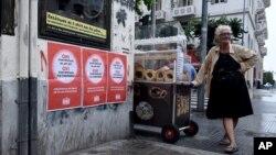 "Seorang nenek penjual roti di sebelah poster bertuliskan ""Tidak untuk proposal Uni Eropa, IMF dan ECB"" di kota Thessaloniki, Yunani (1/7). (AP/Giannis Papanikos)"