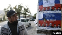 A local resident looks at election campaign posters, which are on display in the village of Vorontsovka near the capital Bishkek, Kyrgyzstan, Oct. 1, 2015.