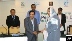 سٹیپ کے نمائندے عاطف شیخ کانفرنس میں شیلڈ وصول کرتے ہوئے