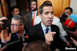 Venezuelan opposition leader and self-proclaimed interim president Juan Guaido talks to the media before a session of the Venezuela's National Assembly, in Caracas, Venezuela, Jan. 29, 2019.